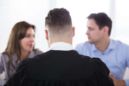 Rear View Of A Male Judge Sitting In Front Of Couple Quarreling Stock Photo