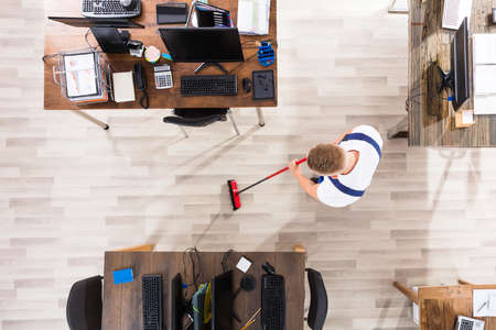 Elevated View Of Male Janitor Cleaning Floor With Broom At Workplace