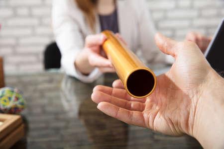 Close-up van een hand passeren gouden estafettestokje naar zakenvrouw