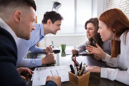 Compañero de trabajo discutiendo entre sí en el lugar de trabajo en la Oficina