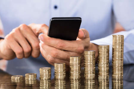 Stack Of Increasing Coins In Front Of The Businessman Using Smart Phone For Calculating Coins Stok Fotoğraf