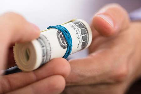 Close-up van een persoon die overhandigt het opgerolde geld aan een andere hand