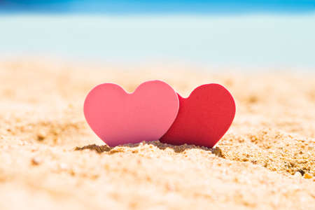 Two Pink And Red Hearts In Sand At Beach Imagens