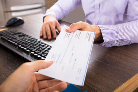 Close-up Of A Businessman Giving Cheque To Her Colleague At Workplace In Office