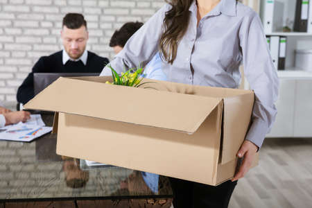 Fired Businesswoman Leaving Office With Her Belongings In Box