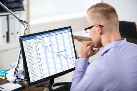 Primer plano de un hombre de negocios que analiza el gráfico de Gantt en la computadora sobre el escritorio de madera Foto de archivo