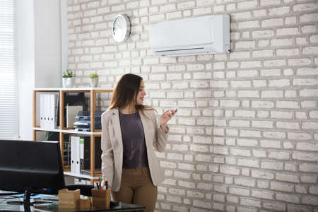 appliances: Young Businesswoman Standing In Office Using Remote Control Of Air Conditioner Stock Photo