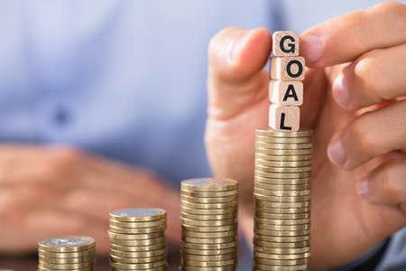 コイン スタックを増加を目標ブロックを持っている手のクローズ アップ