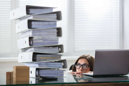 Young Businesswoman Peering At The Stack Of Folders In Curiosity From Behind The Desk