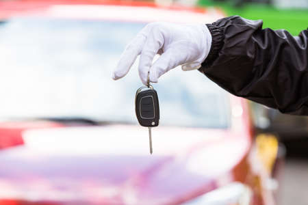 Close-up Of A Valet Wearing Glove Holding Car Key