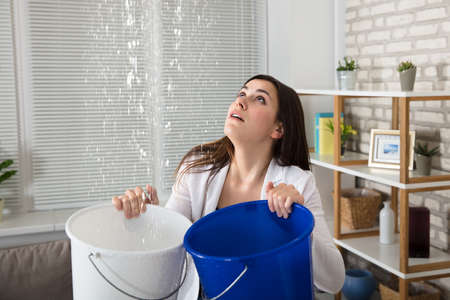 Worried Woman Holding Two Buckets While Water Droplets Leaking From Ceiling Stockfoto