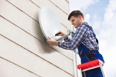 Junger männlicher Techniker in der Uniform, die Fernsehsatellitenschüssel an der Wand installiert Standard-Bild