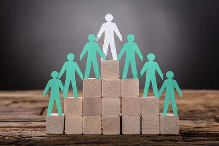 Nahaufnahme des Papierchefs mit den Angestellten, die auf Holzklötzen stehen Standard-Bild - 82522957