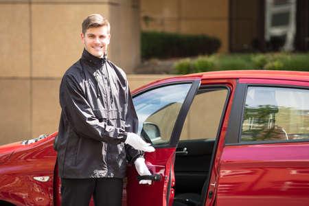 Portrait Of A Happy Young Male Valet Opening Red Car Door Foto de archivo