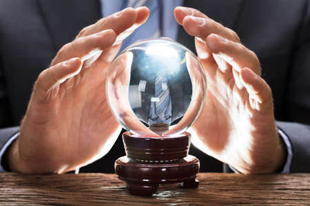 Midsection of businessman covering crystal ball at wooden table Stok Fotoğraf