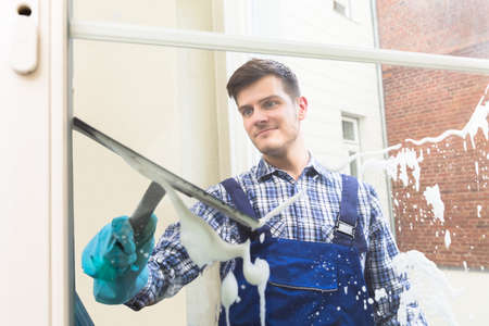 Young Male Housekeeper In Uniform Cleaning Window With Squeegee
