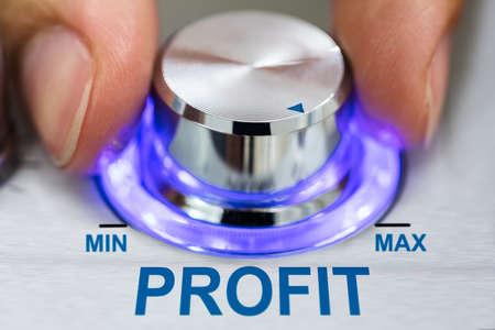 Cropped image of hand turning illuminated metallic knob by profit text