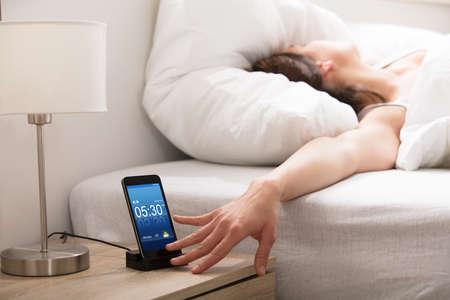 Vrouw Die Het Alarm Op Mobiele Telefoon Zet Tijdens Wakker In De Ochtend Stockfoto