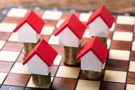 Closeup of house models on stacked coins on chessboard Stock Photo