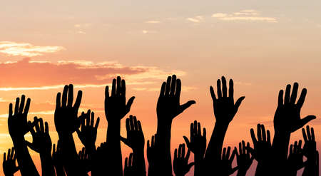 Silhouette Of Raised Hands Against The Dramatic Sky At Sunset Stock Photo