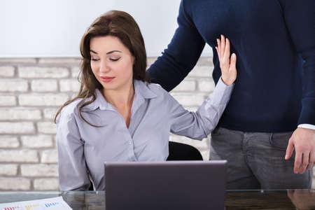 Jovem mulher defendendo-se para o assédio sexual no escritório de negócios Foto de archivo