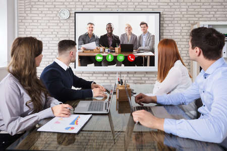 Groep bedrijfsmensen die videoconferentie doen tijdens zakelijke bijeenkomst op kantoor