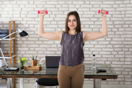 Smiling Young Businesswoman Doing Exercise With Pink Fitness Dumbbells In Office