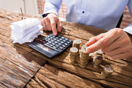 Close-up Of A Business Person Counting Coins Using Calculator With Pink Piggybank Over The Desk Standard-Bild