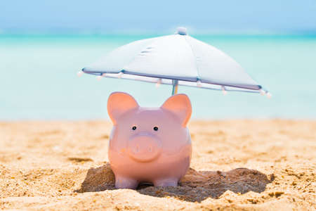Pink Piggy Bank Under The Small Parasol During Summer At Beach Фото со стока