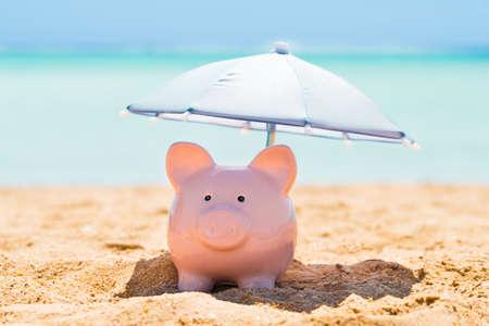 Roze spaarvarken onder de kleine parasol tijdens de zomer op het strand