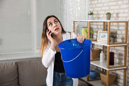 Worried Woman Calling Plumber While Collecting Water Droplets Leaking From Ceiling At Home Фото со стока - 83075516