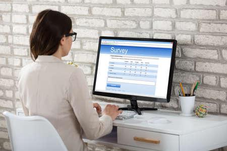オフィスにあるコンピューター上のアンケート フォームを充填実業家の後姿
