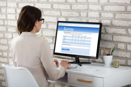 Rear View Of A Businesswoman Filling Survey Form On Computer In Office Stock Photo