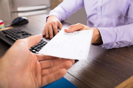 職場のオフィスで同僚に小切手を与える実業家のクローズ アップ