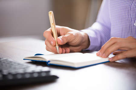 Businessman Writing On Diary With Golden Pen On Desk At Workplace