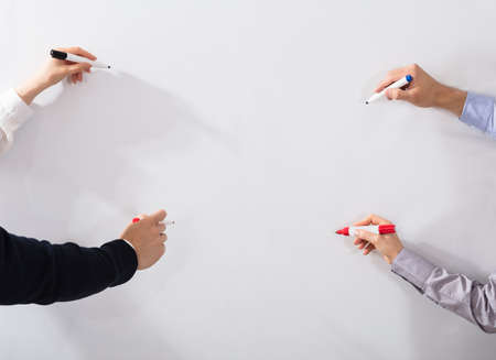 Close-up Of Business Peoples Hands Holding Different Marker Writing On Whiteboard Фото со стока