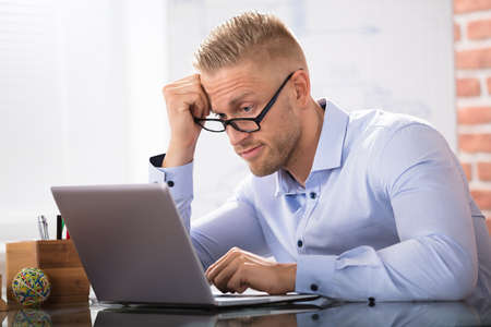 contemplated: Contemplated Businessman Sitting With Laptop At Workplace