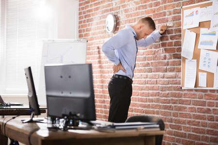 Empresario apoyado contra la pared de ladrillo con dolor de espalda en la oficina Foto de archivo