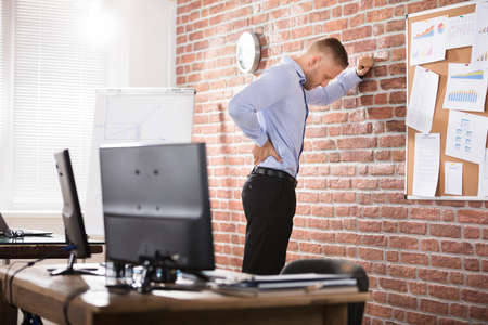Zakenman Leuning Against The Brick Wall Having Back Pain In Office