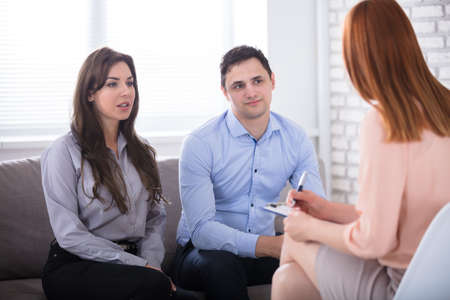 psychologists: Young Couple Sitting With Psychologist In Office