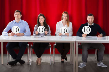 Happy Panel Judges Sitting In Front Of Red Curtain Showing 10 Score Signs