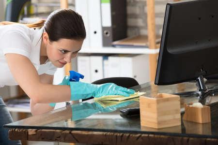 Szczęśliwa Młoda Kobieta Czyszczenia Szklanych Biurko Z Rag Zdjęcie Seryjne