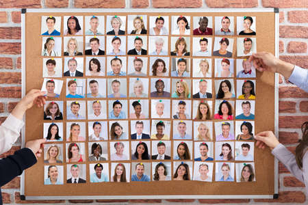 Close-up Of Business People Hiring The Candidates Attached On Corkboard For Job photo