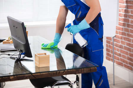 Close-up Of A Male Janitor Cleaning Desk With Cloth In Office Standard-Bild