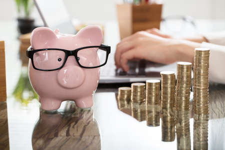 Piggy Bank And Increasing Coins Stack In Front Of A Person Using Laptop At Workplace Stock Photo - 82969386