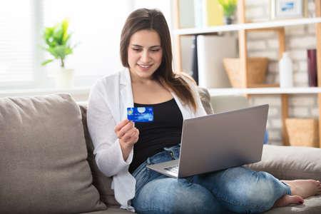 집에서 신용 카드를 들고 노트북과 소파에 앉아 웃는 젊은 여자