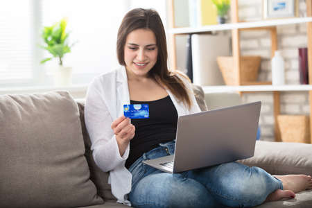 A Smiling Young Woman Sitting On Couch With Laptop Holding Credit Card At Home