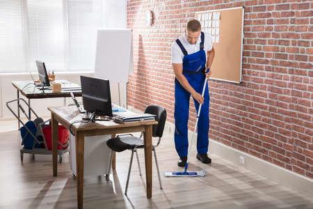 若い男性用務員職場で堅木張りの床を拭く 写真素材