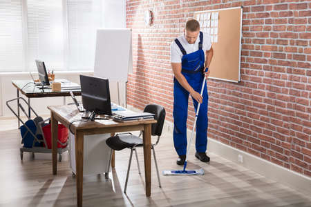 Young Male Janitor Mopping Hardwood Floor At Workplace Reklamní fotografie - 82979385