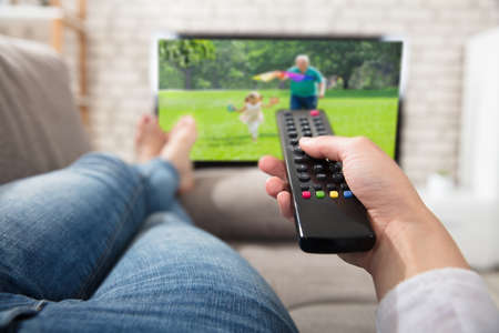 Close-up Of A Woman Changing The Channel With Remote Control While Watching Television Stock Photo